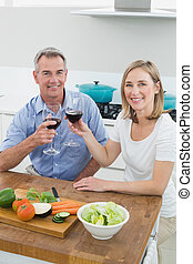 Couple toasting wine glasses in kitchen - Portrait of a...