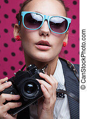 Close Up of fashionable girl with old camera in blue...