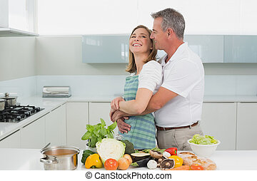 Side view of a man embracing woman in kitchen