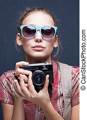 Trendy girl in glasses playing the ape with camera....