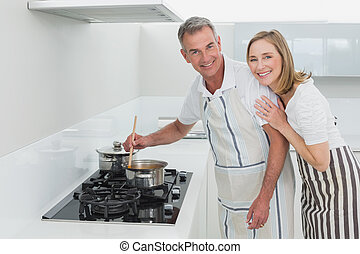Happy couple preparing food in kitchen - Portrait of a happy...
