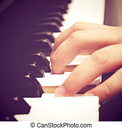 Close up of hand playing piano with retro filter effect