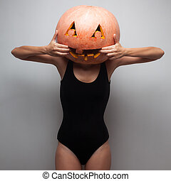 Slim body model playing the ape with pumpkin on the head