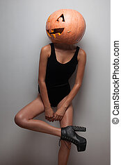 Fashionable slim model posing with pumpkin on head indoors