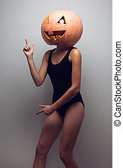 Dancing go-go female dancer with halloweens pumpkin on head