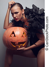 Fashionable model posing with halloween pumpkin