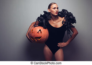 Fashionable female model holding halloweens pumpkin Studio...