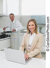 Businesswoman using laptop while man preparing food in...
