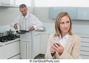 Businesswoman text messaging while man preparing food in the...