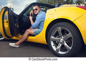 Lucky young man sitting in his new convertible car. Low...