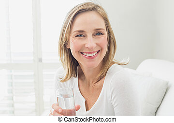 Portrait of a smiling relaxed woman with a glass of water in...