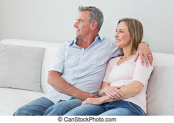Relaxed couple sitting on sofa with arm around - Happy...