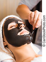 skin care, beautician applying face mask cream