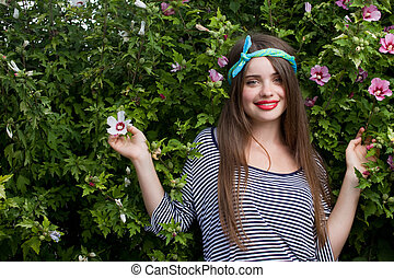 trendy teenager model with kerchief posing with flowers...