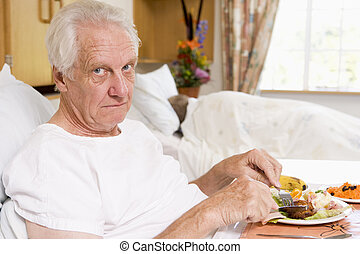 Senior Man Eating Hospital Food In Bed