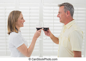 Side view of a couple toasting wine glasses - Side view of a...