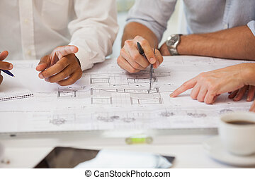 Mid section of business people working on blueprints -...