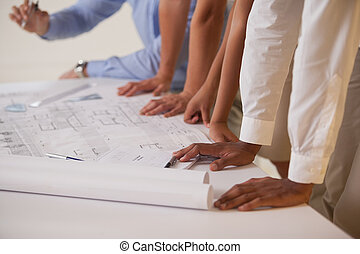 Mid section of business people working on blueprints in...