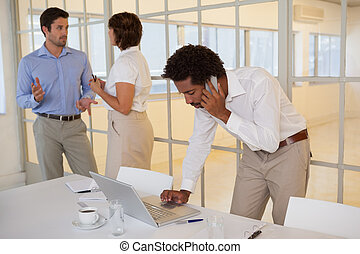 Young businessman using laptop and cellphone with colleagues...