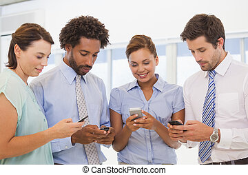 Smiling business colleagues text messaging in the office