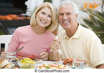 Couple Enjoying A Barbequed Meal In The Garden