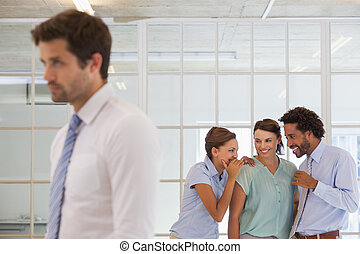 Colleagues gossiping with sad businessman in foreground -...