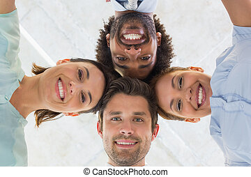 Business team forming a huddle - Low angle portrait of...