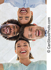 Business team with heads together forming huddle - Low angle...