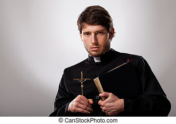Priest with cross and holy bible - Young priest is holding a...