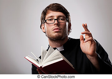 Priest with Holy Bible - Young christian priest in glasses...