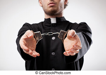 Priest handcuffed - Young christian priest in cassock...