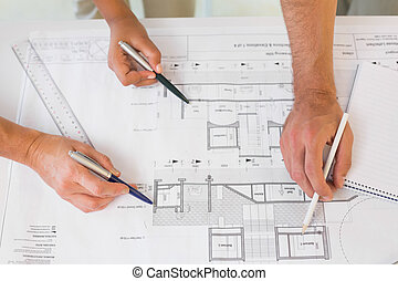 Extreme close-up of hands working on blueprints