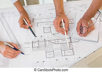 Several hands working on blueprints - Extreme close-up of...