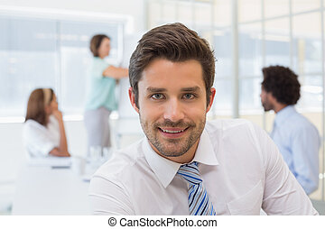 Smiling businessman with colleagues in meeting at office -...