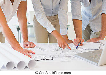 Mid section of business people working on blueprints at...