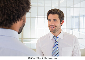 Smiling businessmen looking at each other in office -...