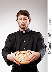 Priest with bread - Young christian priest is blessing the...