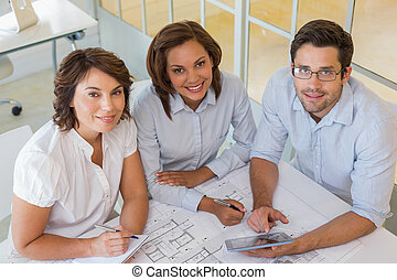 Portrait of young business people working on blueprints and...