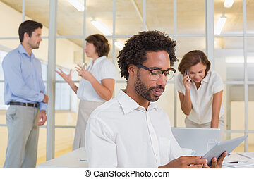 Concentrated young businessman using digital table with colleagues in background at office