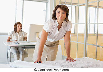 Portrait of a young businesswoman working on blueprints with...