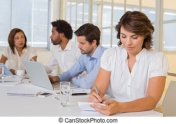 Concentrated young businesswoman writing notes with colleagues in meeting at the office
