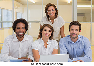 Smiling business people using laptop at office - Portrait of...