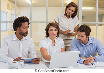 Business people using laptop in meeting at office
