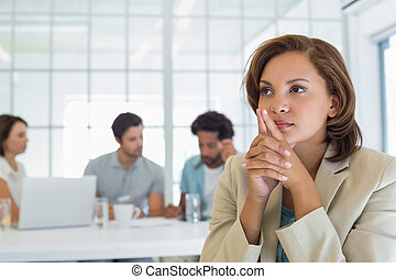 Close-up of serious businesswoman with colleagues in meeting...