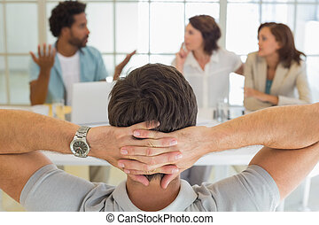 Rear view of relaxed businessman with colleagues in meeting...