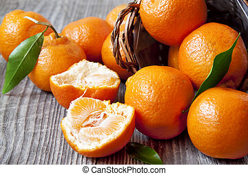 Clementines - Fresh Clementines on Wooden Board with Leaves