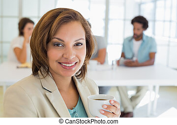 Smiling businesswoman having coffee with colleagues in...