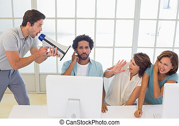 Man yelling through megaphone at business people - Man...