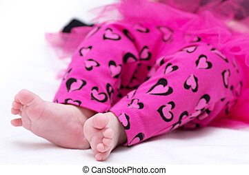 Newborn baby girl feet in pink clothes