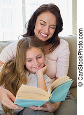 Woman and daughter reading story book - Happy woman and...